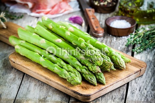 Fresh organic asparagus on a cutting board with Parma ham : Stock Photo