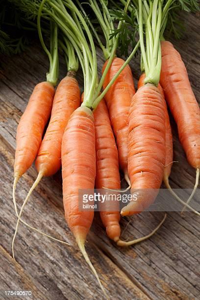 Fresh organic carrots on rustic wood table