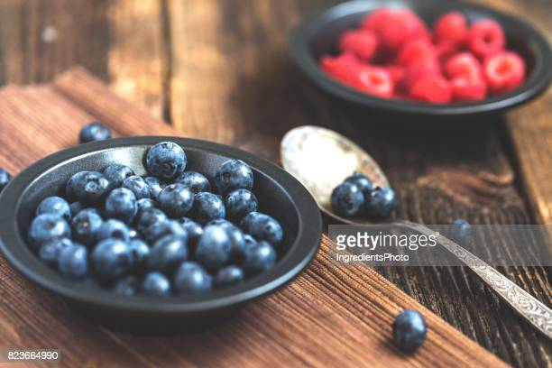 Fresh organic strawberries and blueberries on a dark rustic metal plate.