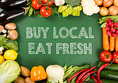 """local produce fresh vegetables on the """"buy local eat fresh"""" sign"""