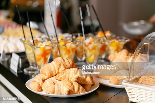 Fresh pastry, crispy morning croissants, hotel breakfast buffet. Dessert fruit cocktail in cups : Stock Photo