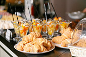 Fresh pastry, crispy morning croissants, hotel breakfast buffet. Dessert fruit cocktail in cups.