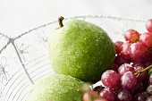 Fresh pears and red grapes in wire basket