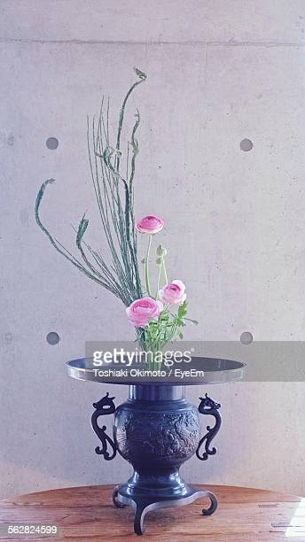 Fresh Pink Flowers In Antique Vase On Table Against Wall