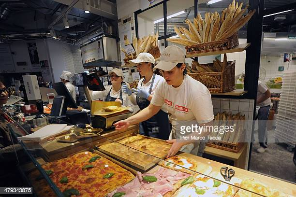 Fresh pizza is prepred and displayed for sale during the opening ceremony of highend mall and market chain Eataly's new Milan store on March 18 2014...