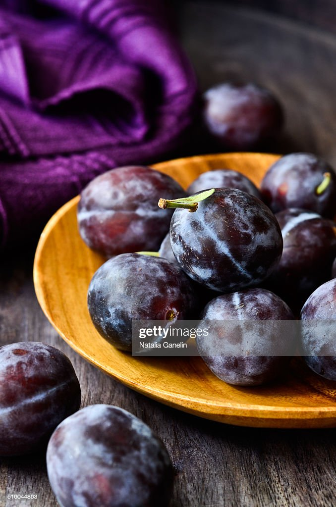 Fresh plums on a wooden plate