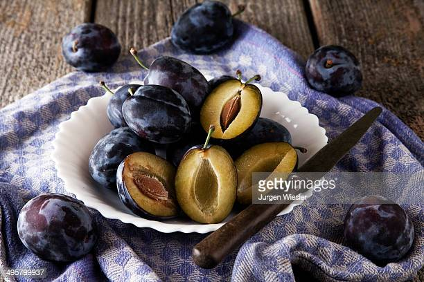 Fresh plums -Prunus domestica- on plate, with a knife and a kitchen towel