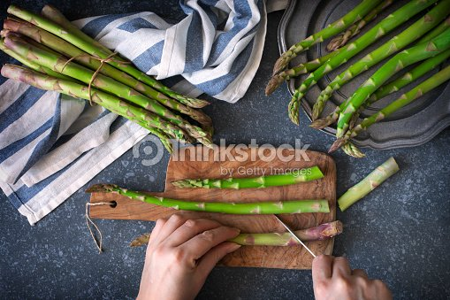 Fresh  raw asparagus on stone background. Women female hands cut asparagus on wooden cooking board. Top view : Stock Photo