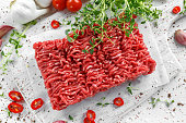Fresh Raw Beef Minced Meat with salt, pepper, chilli and fresh thyme on white board
