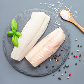 Fresh raw cod fillet with spices, pepper, salt, basil on a stone plate, top view, square