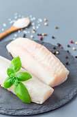 Fresh raw cod fillet with spices, pepper, salt, basil on a stone plate, vertical, copy space