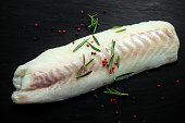 Fresh Raw Cod loin fillet with rosemary, cracked pepper on stone board.