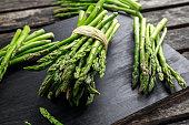 Fresh raw green Asparagus on wooden chopping board.