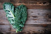 Fresh raw green superfood kale curly cabbage leaves on wooden background