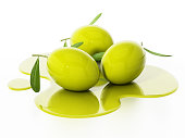 Fresh raw olives with green leaves in spilled olive oil.