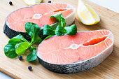 Fresh raw salmon steaks on wooden board