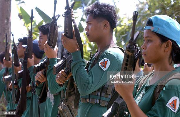 Fresh recruits of the communist New People's Army guerrillas stand in formation with their firearms mostly stolen from Philippine government troops...