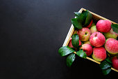 Fresh red apples in the wooden box on black background.  Top view. Copy space