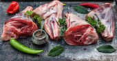 Fresh red meat, chops with spices,pepper, peperoni, herbs, rosemary, parsley on old metal tray, top view, copy space