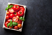 Fresh ripe garden tomatoes and basil on stone table. Top view with copy space