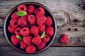 Fresh ripe organic raspberries in a plate on a wooden background
