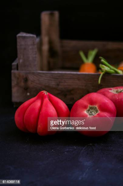 fresh ripe organic  tomatoes and carrot on a dark background