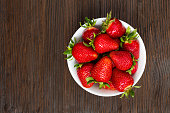 Fresh ripe strawberries in a simple white bowl, on dark wooden table