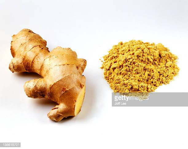 Fresh root ginger with pile of ginger powder