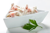 Fresh salad in bowl made from meat and mayonnaise on white with parsley