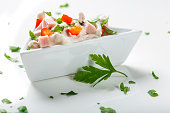 Fresh salad in bowl made from meat, red pepper and mayonnaise on white with parsley