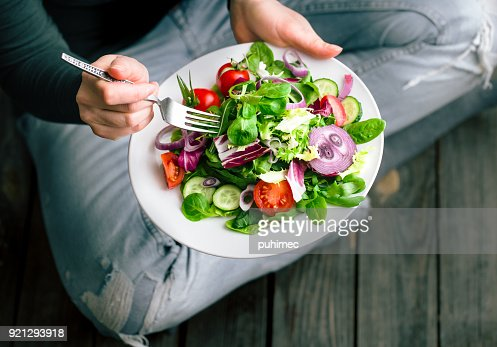 Fresh salad in hands view from above : Stock Photo