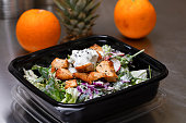 Fresh salad meal packed in a plastic container ready to eat - Healthy takeaway food and eating concept. Shot in a real healthy fast food kitchen, ready for delivery.