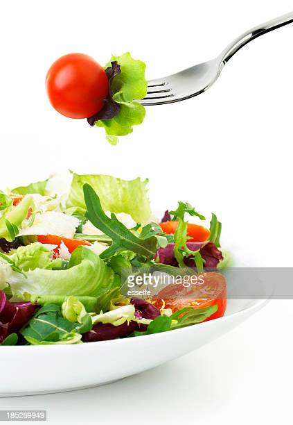 Fresh salad plate with fork picking up a cherry tomato