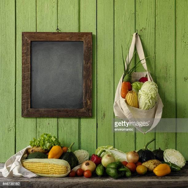 古い緑の木の板壁に掛かっている木製組み立てられた空の黒板の横に天然コットンの再利用可能な袋に新鮮なサラダ野菜。