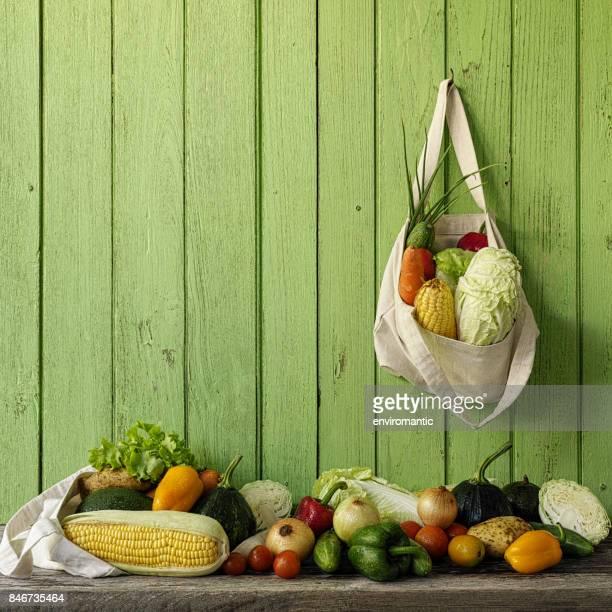 古い緑の木の板壁に掛かっている自然綿の再利用可能な袋に新鮮なサラダ野菜。