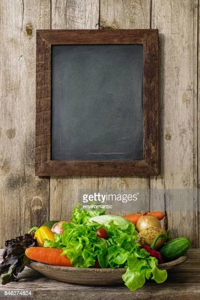古い木の板壁に掛かっている木製の組み立てられた空白黒板の下にある古い木製のボウルでサラダ野菜。