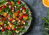 Fresh salad with arugula, fruits and nuts. Healthy food.