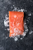 Fresh salmon fillet on ice. Dark slate background. Top view.