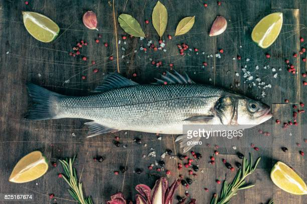 fresh sea bass arranged on rustic wooden kitchentable