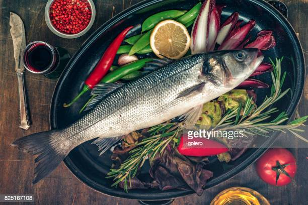 fresh sea bass in cooking pot on kitchentable