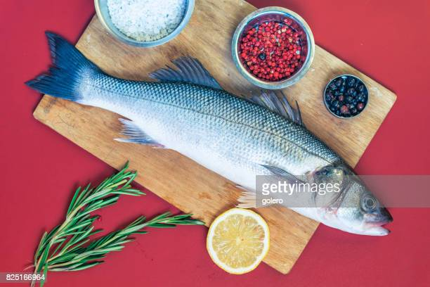 fresh sea bass on red kitchentable
