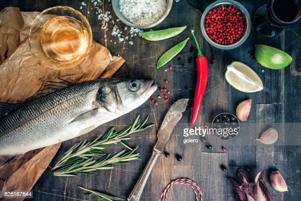 fresh sea bass on wooden kitchentable
