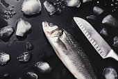 Raw sea bass with ice and knife at black background. Minimalistic mockup for seafood restaurant or fish market. Top view, copy space