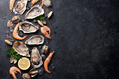 Fresh seafood on stone table. Oysters, prawns and shells. Top view with copy space