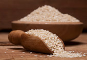 Fresh sesame seeds in a wooden bowl and spoon on wooden background