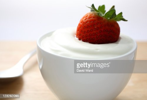 A fresh strawberry dipped in a bowl of yogurt. : Stock Photo