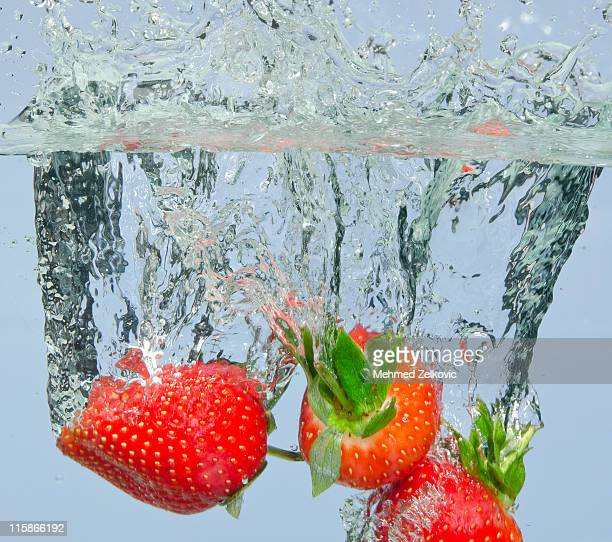 Fresh strawberry dropped into water