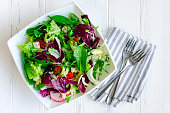 Fresh summer green salad mix with salad lettuce, spinach, fennel, celery, tomatoes, radish, olives, chicory and arugula in white bowl with forks on wooden background. Healthy eating concept. Top view.