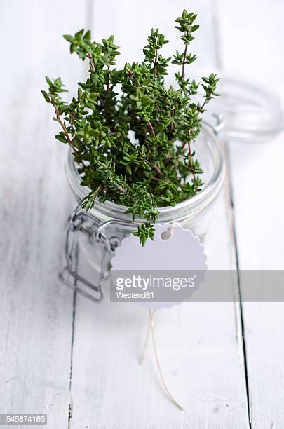 Fresh thyme in a preserving jar on wood