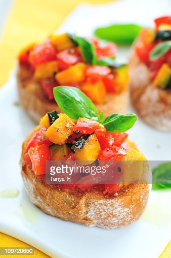 Fresh tomato and roasted pumpkin bruschetta on a white plate